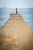 O homem no quebra-mar Imagens de Stock