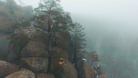 O homem no revestimento amarelo escala as rochas cobertas com a névoa filme