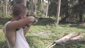 O homem no revestimento branco está disparando de uma besta vídeos de arquivo