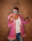 O homem no revestimento cor-de-rosa escuta a música Fotos de Stock