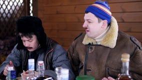O homem no revestimento senta-se em torno da tabela com alimento ao lado de seu amigo com as aletas da orelha do chap?u filme