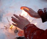O homem no revestimento vermelho para aquecer as mãos congeladas fotografia de stock