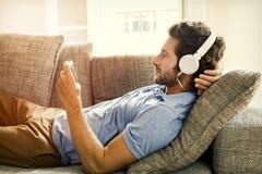 O homem no sofá olha um filme no telefone celular Fotografia de Stock Royalty Free