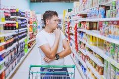 O homem no supermercado, cliente que pensa, escolhe o que comprar fotos de stock