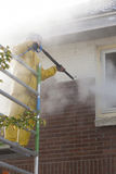 O homem no terno amarelo da chuva limpa a pintura da parede de tijolo do fá da casa imagem de stock royalty free