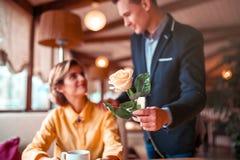 O homem no terno dá a flor cor-de-rosa à mulher feliz nova fotografia de stock royalty free