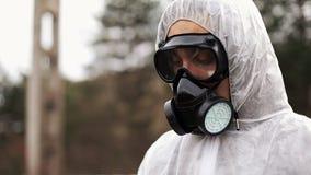 O homem no terno da gás-máscara e do bio-perigo olha abaixo de tomar notas em sua tabuleta filme