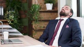 O homem no terno de negócio caiu adormecido em sua mesa video estoque