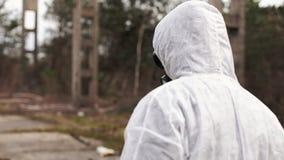 O homem no terno do bio-perigo e na máscara de gás anda ao stipe na terra completamente do desperdício vídeos de arquivo