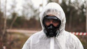 O homem no terno do bio-perigo e na máscara de gás anda e olha em linha reta na câmera filme