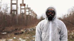 O homem no terno do bio-perigo e na máscara de gás está antes da fábrica vídeos de arquivo