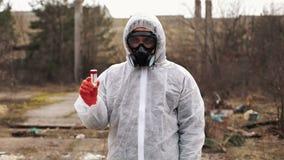 O homem no terno do bio-perigo e na máscara de gás está antes da fábrica video estoque
