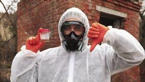O homem no terno do bio-perigo e na máscara de gás mostra a água contaminada e sinais não-verbais video estoque