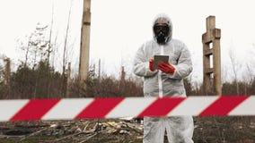 O homem no terno do bio-perigo e na máscara de gás toma fotos em seu smartphone filme