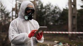 O homem no terno do bio-perigo e na máscara de gás toma notas em sua tabuleta que está na terra poluída vídeos de arquivo