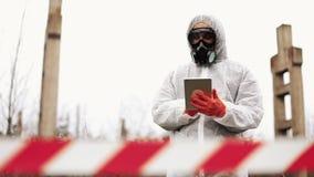 O homem no terno do bio-perigo e na máscara de gás toma notas em sua tabuleta que está na terra poluída filme
