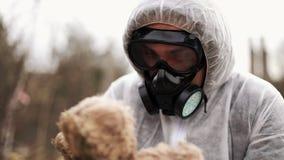 O homem no terno do bio-perigo e na máscara de gás toma um brinquedo em seus braços filme