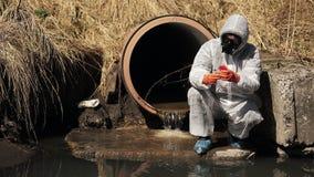O homem no terno do bio-perigo e na máscara de gás verifica a poluição da água fora filme