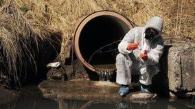 O homem no terno do bio-perigo e na máscara de gás verifica a poluição da água fora video estoque