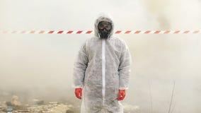 O homem no terno e no gás do bio-perigo anda à zona poluída coberta com o fumo filme
