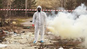 O homem no terno e no gás do bio-perigo anda à zona poluída coberta com o fumo video estoque