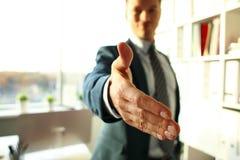 O homem no terno e o laço dão a mão como olá! foto de stock