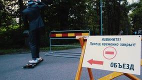 O homem no terno e o chapéu montam na colisão do skate na cerca na estrada Árvore no campo vídeos de arquivo