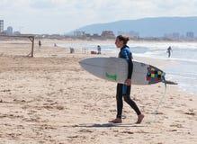 O homem no terno impermeável da cor anda na praia com placa Imagem de Stock Royalty Free