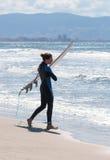 O homem no terno impermeável da cor anda na praia com placa Imagens de Stock Royalty Free