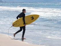 O homem no terno impermeável da cor anda na praia com placa Imagens de Stock