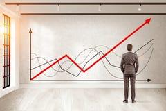 O homem no terno marrom está olhando gráficos Imagem de Stock