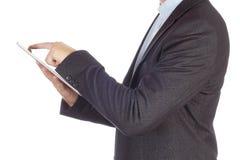 O homem no terno preto está usando a tabuleta isolada no fundo branco Homem de negócios com tabuleta Fotografia de Stock
