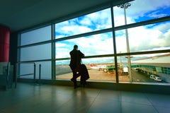 O homem no terno preto que espera um voo Imagens de Stock Royalty Free