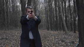 O homem no terno toma o alvo com uma arma Apronte para disparar vídeos de arquivo
