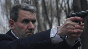 O homem no terno toma o alvo com uma arma Apronte para disparar Fim acima vídeos de arquivo