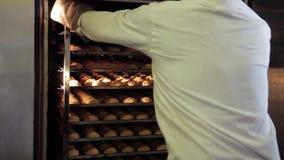 O homem no uniforme branco leva embora cookies cozidas na fábrica da padaria vídeos de arquivo
