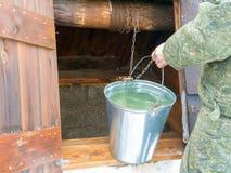O homem no uniforme militar pegara a água de um poço no inverno foto de stock