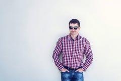 O homem no verão contra a parede, vidros, olhares sérios na parte dianteira, nas calças de brim e em uma camisa, dia ensolarado b Fotografia de Stock Royalty Free