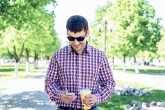 O homem no verão no parque, lendo uma mensagem em seu telefone, vidros, olhando o socia do mapa e do feed noticioso Fotografia de Stock