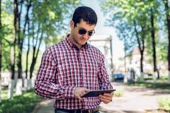 O homem no verão no parque, nos vidros de leitura, olhando um mapa e um feed noticioso em redes sociais, fil video de observação Imagem de Stock