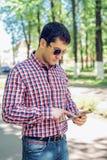 O homem no verão no parque, nos vidros de leitura, olhando um mapa e um feed noticioso em redes sociais, fil video de observação Imagens de Stock