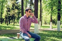 O homem no verão no parque, relaxando com uma xícara de café ou um chá, chamando os vidros vestindo do telefone, calças de brim Imagens de Stock Royalty Free