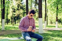 O homem no verão no parque, relaxando com uma xícara de café ou um chá, lendo sms em vidros vestindo do telefone, ne Imagem de Stock