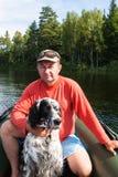 O homem no vermelho com um cão Lago Tagasuk, Sibéria, Rússia fotografia de stock royalty free