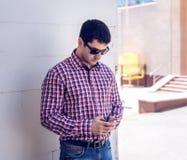 O homem nos óculos de sol da camisa e das calças de brim, guardando o telefone celular, leu as mensagens no seu, o conceito da co Fotografia de Stock Royalty Free