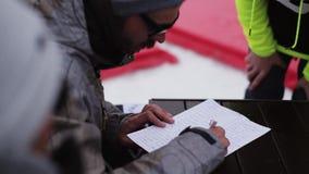 O homem nos óculos de sol redige a lista de participantes na competição na estância de esqui cavaleiros video estoque
