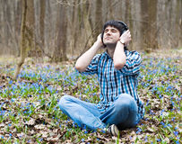 O homem nos auscultadores meditate na madeira da mola fotografia de stock