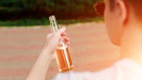 O homem nos vidros com a garrafa do baixo álcool bebe à disposição imagem de stock royalty free
