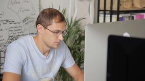 O homem nos vidros e nos fones de ouvido trabalha com cuidado no escritório antes do monitor filme