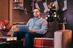 O homem nos vidros guarda o portátil e a vista da câmera ao sentar-se no sofá no tempo do Natal imagens de stock